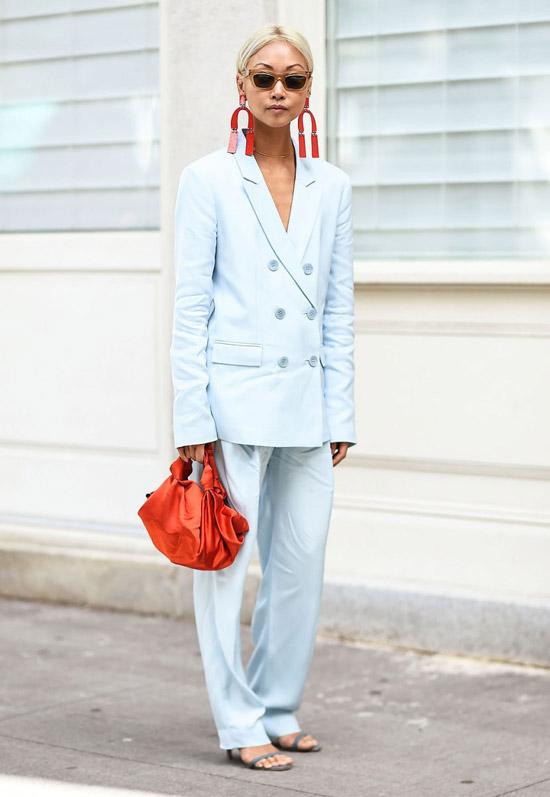 1 девушка в голубом брючном костюме, босоножках и крупных серьгах