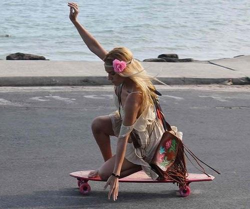 Девушка хиппи едет на скейте, у нее сумка украшенная бахромой и цветочный венок на голове