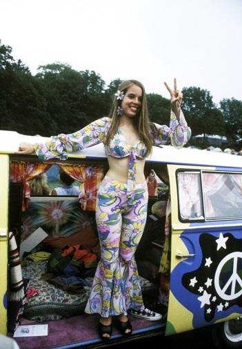 Девушка хиппи стоит в фургоне со знаком пацифист