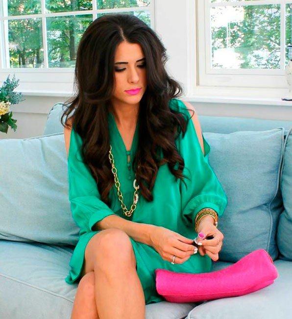 Девушка сочетает зеленое платье с крупными золотыми украшениями и розовой помадой