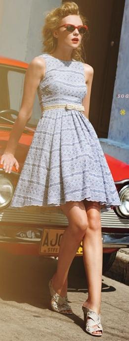 Девушка стоит возле машины в платьице ретро стиля 70-х