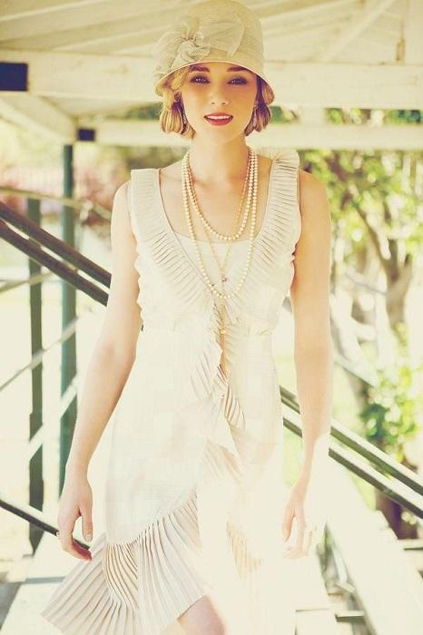 Девушка в белом платье и шляпке, образ украшен длинными бусами в несколько рядов