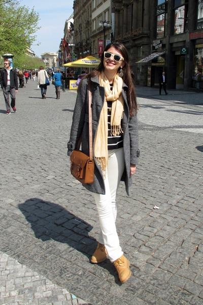 Девушка в белых брюках, сером пальто, шарфом на шее и тимберлендах