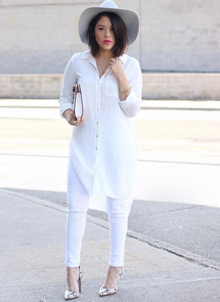 Девушка в белых джинсах и удлиненной белой блузе, шляпа