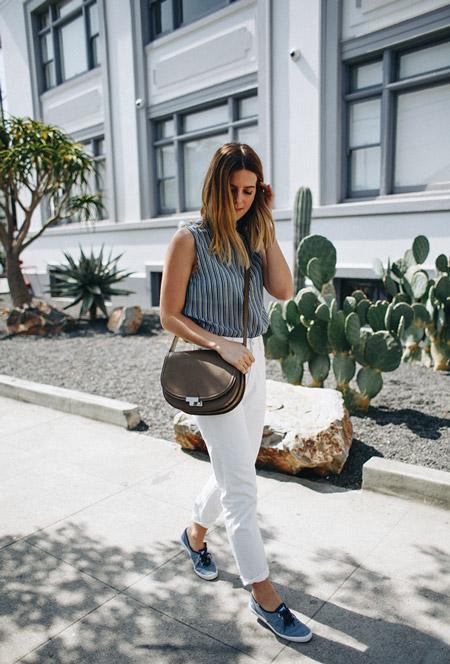 Девушка в белых джинсах, полосатый топ и кеды