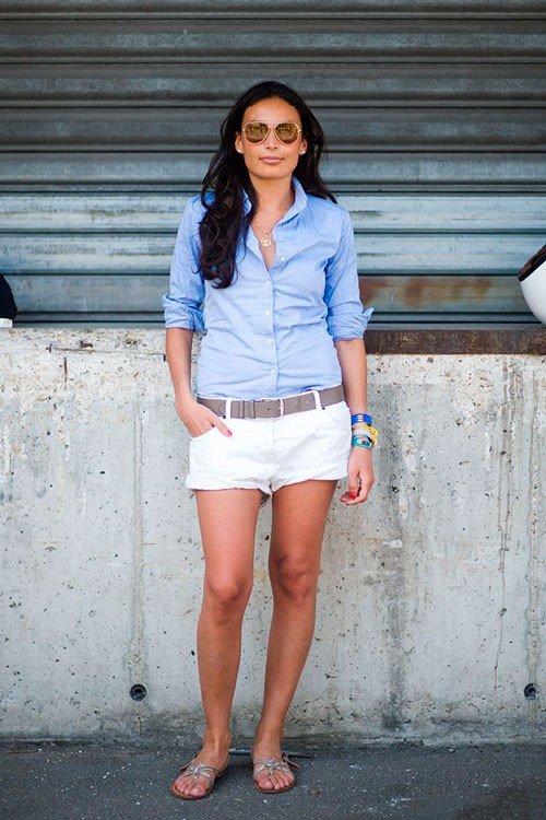 Девушка в белых шортах, голубой рубашке и сандалях