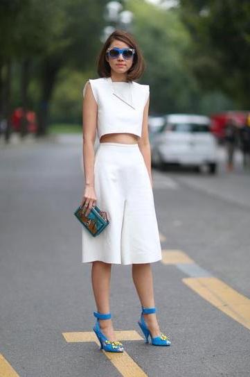 Девушка в белых шортах - кюлоты, коротком топе и голубых босоножках