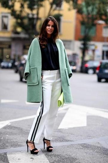 Девушка в белых штанах с лампасами по бокам, чеонлй блузе и пальто