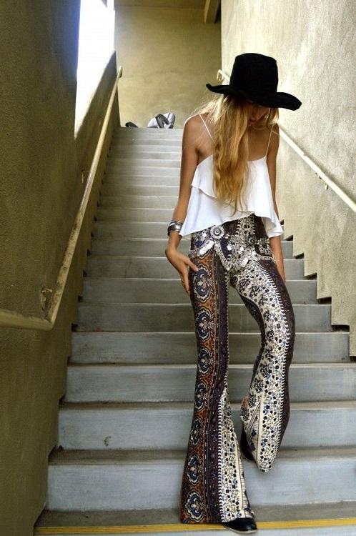 Девушка в брюках-клешь, белом топе и шляпе