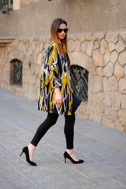 Девушка в чехных легинсах и черных туфлях на шпильке, в пальто с принтом
