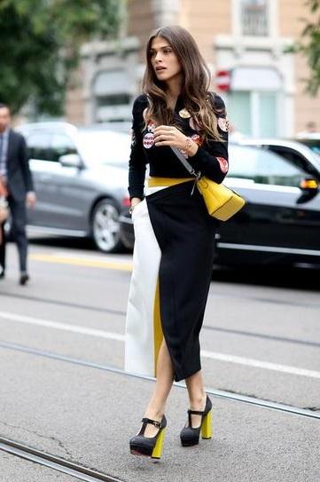 Девушка в черно-бело-желтой юбке и кофте с нашивками