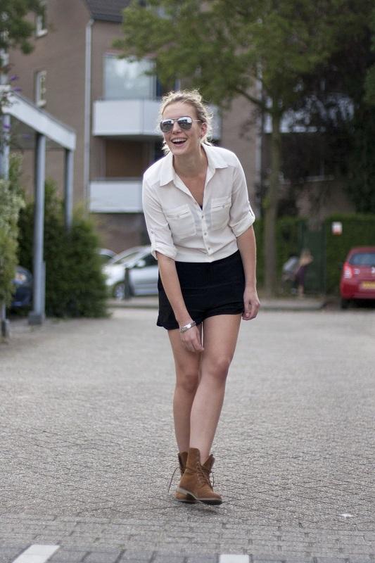 Девушка в черной юбке, белой блузе и тимберлендах