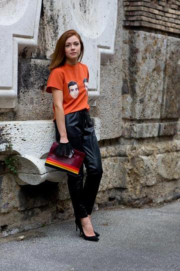 Девушка в черных, кожаных штанах и оранжевой футболке с принтом мужской головы