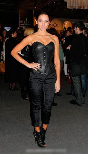 Девушка в черных, облегающих штанах и черном корсете в стиле вамп