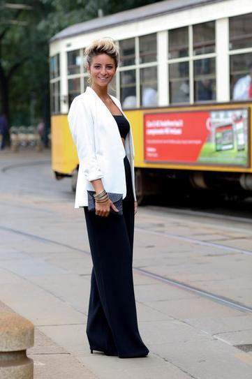 Девушка в черных, широких брюках в пол и белом пиджаке
