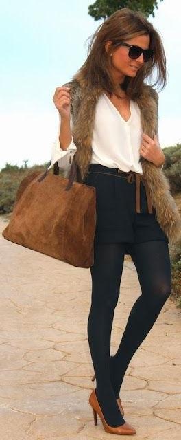 Девушка в черных шортах, чулках, туфлях лодочках и длинном меховом жилете