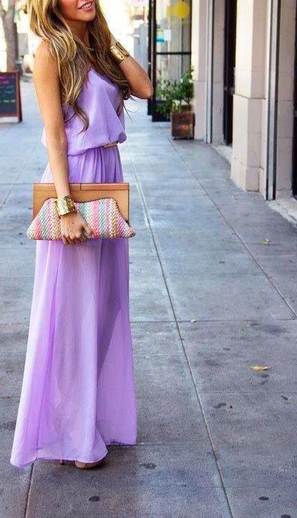 Девушка в длинном, фиолетовом платье с ремнем на поясе и клатчем