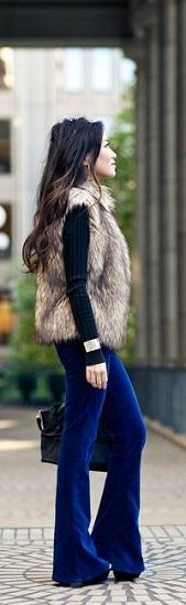 Девушка в длинных брюках клеш и меховом жилете
