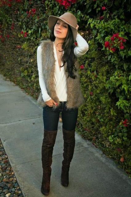 Девушка в джинсах, ботфортах, меховом жилете и ковбойской шляпе