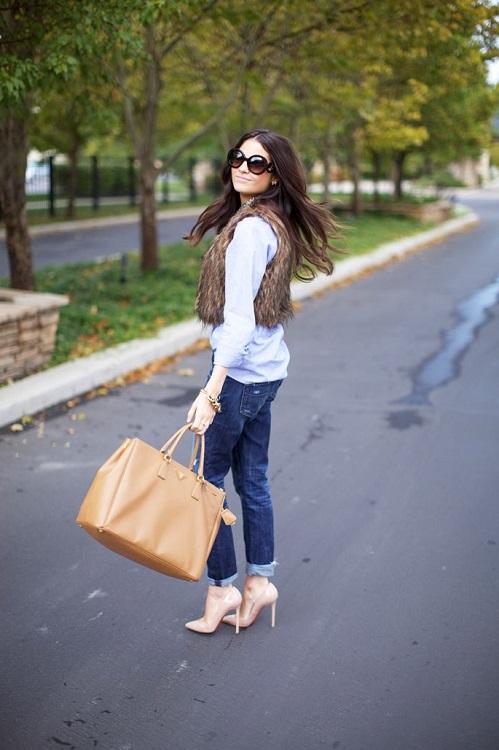 Девушка в джинсах бойфрендах, коротком меховом жилете и туфлях на высоченной шпильке