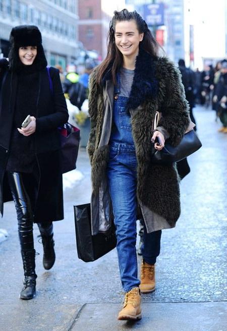Девушка в джинсовом комбинезоне и тимберлендах