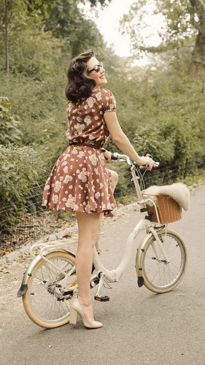 Девушка в коротеньком, коричневом платье с цветочным принтом на велосипеде