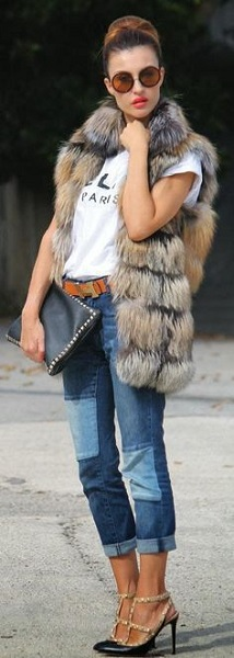 Девушка в коротких джинсах бойфрендах, меховом жилете и туфлях на каблуке