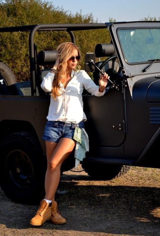 Девушка в коротких, джинсовых шортиках, белой блузе и светло-коричневых тимберлендах