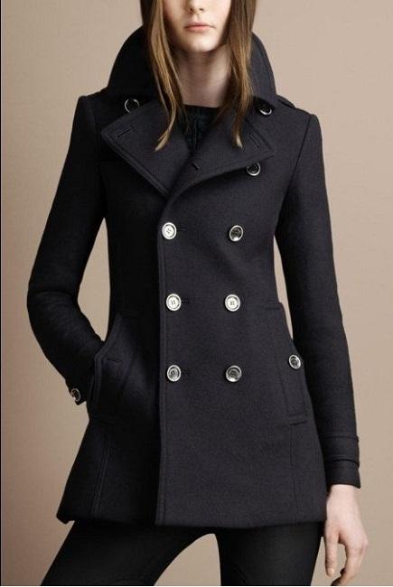 Девушка в коротком, простом, черном пальто на пуговицах