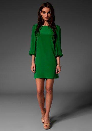 Девушка в коротком зеленом платье, бежевых туфлях и украшениях из золота