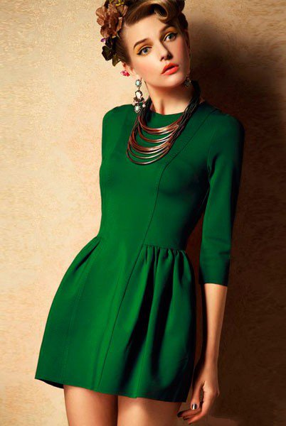 Девушка в коротком зеленом платье с крупным ожерельем на шее и сережками