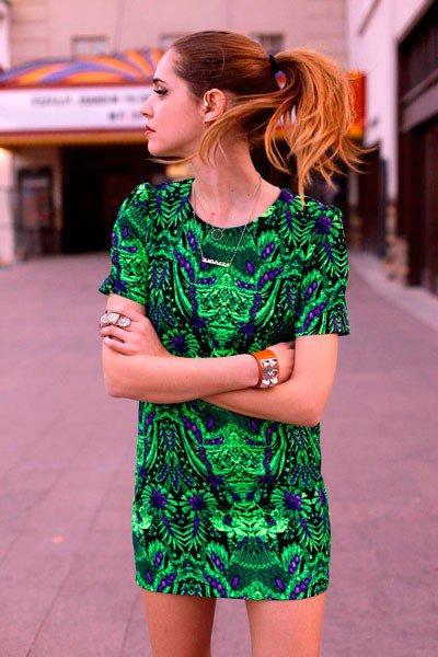 Девушка в коротком, зеленом платье спринтом, браслетом на руке и золотой цепочкой