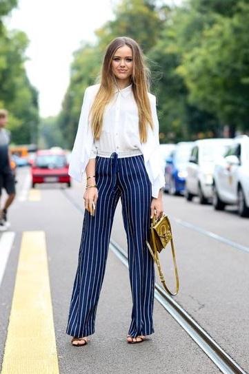 Девушка в красивых полосатых штанах и белой блузе