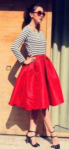 Девушка в красной, пышной юбке миди, полосатом топе и туфлях на каблуке