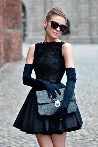 Девушка в маленьком черном платье и перчатках