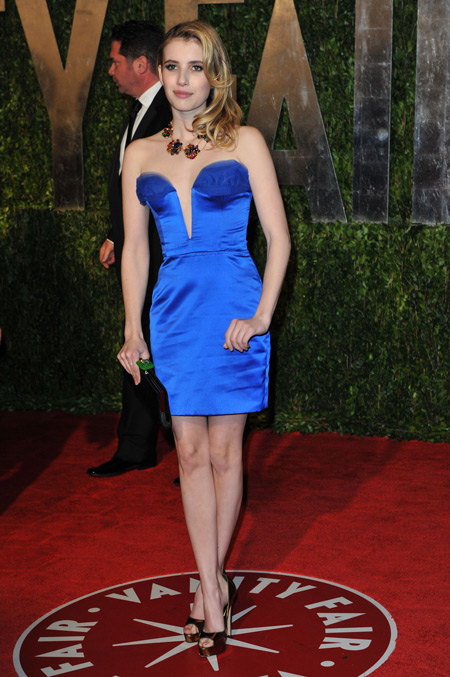 Девушка в мини платье синего цвета с глубоким вырезом без рукавов