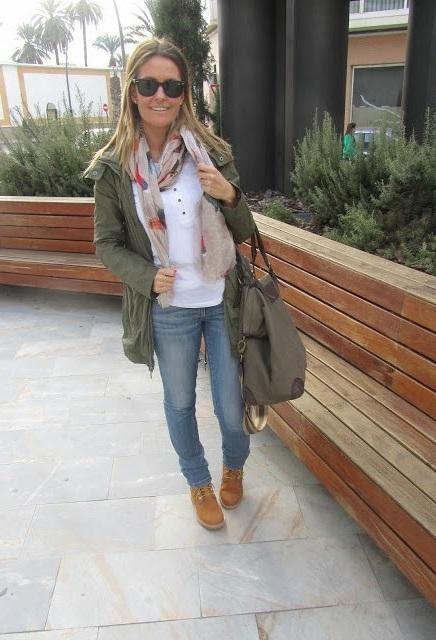 Девушка в обтягивающих джинсах, белой футболке, тимберлендах и куртке