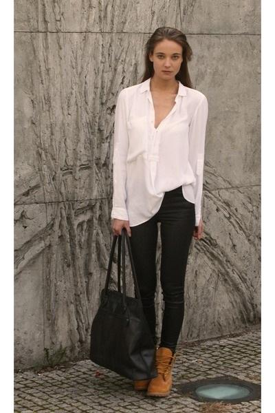 Девушка в обтягивающих джинсах, тимберлендах и небрежно заправленной блузой