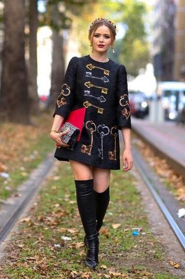 Девушка в очень модном, коротеньком платьице с принтами ключей и ботфортах