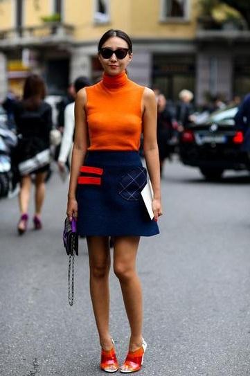 Девушка в оранжевом топе и синей, короткой юбке