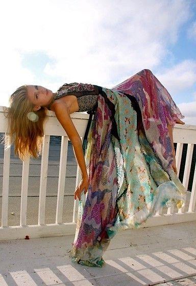 Девушка в платье стиля хиппи лежит на перелах