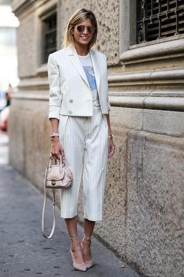 Девушка в полосатом костюме состоящем из жакета и укороченных брюк и футболке