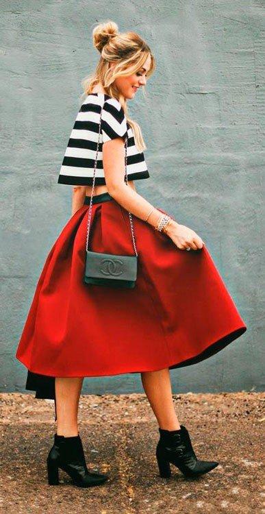 Девушка в пышной юбке миди, полосатом топе и черной сумочкой Шанель