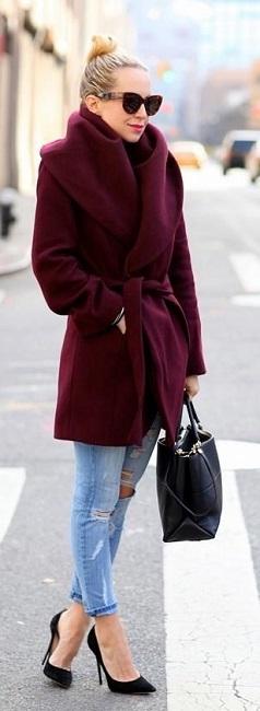 Девушка в рваных, голубых джинсах пальто сливового цвета
