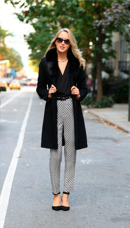 Девушка в серых штанах с принтом, черных туфлях и черном пальто