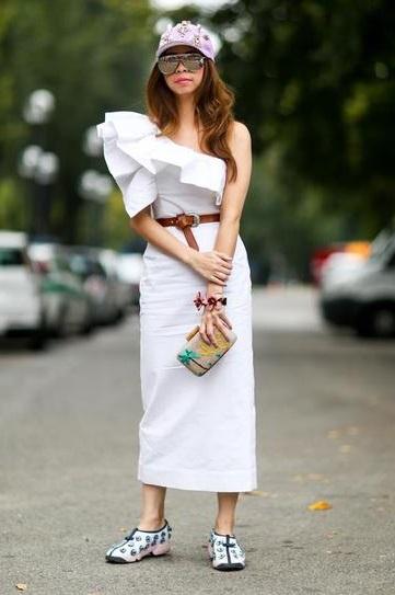 Девушка в шикарном, белом платье и кроссовках с шипами