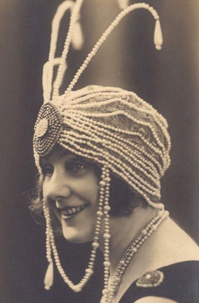Девушка в шляпке украшенной бусами в стиле Гетсби