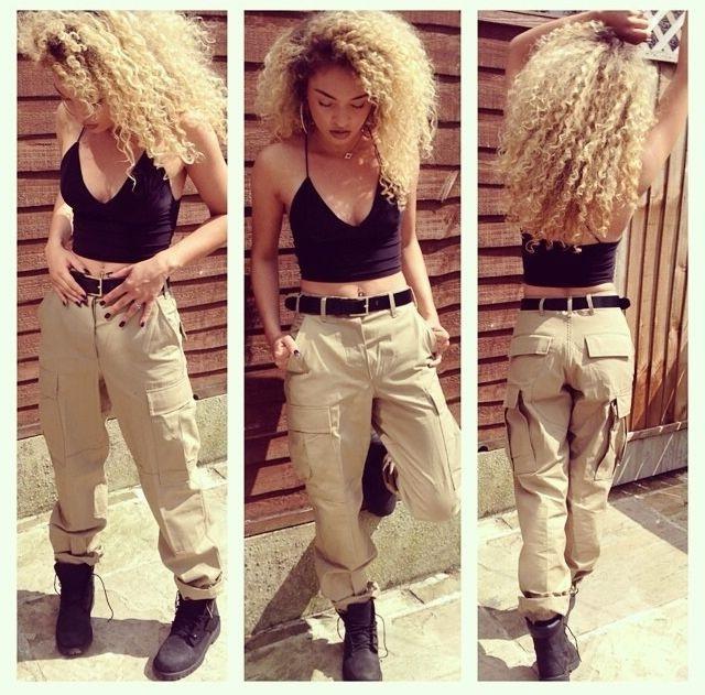 Девушка в штанах стиля сафари, черных тимберлендах и топе