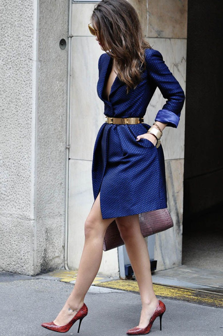 Девушка в синем платье с глубоким вырезом и золотым поясом на талии
