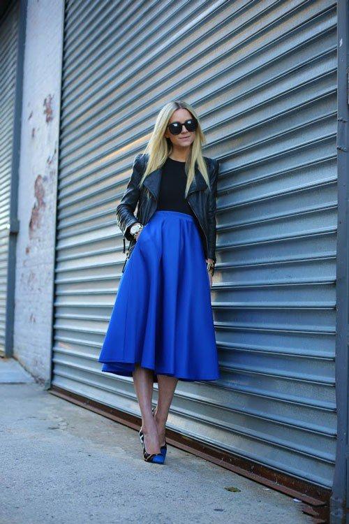 Девушка в синей, расклешенной юбке миди с высокой талией, черной кожаной куртке и просто изумительных туфлях